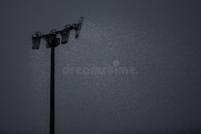 L'éclairage de mât brille sur la neige en baisse photographie stock