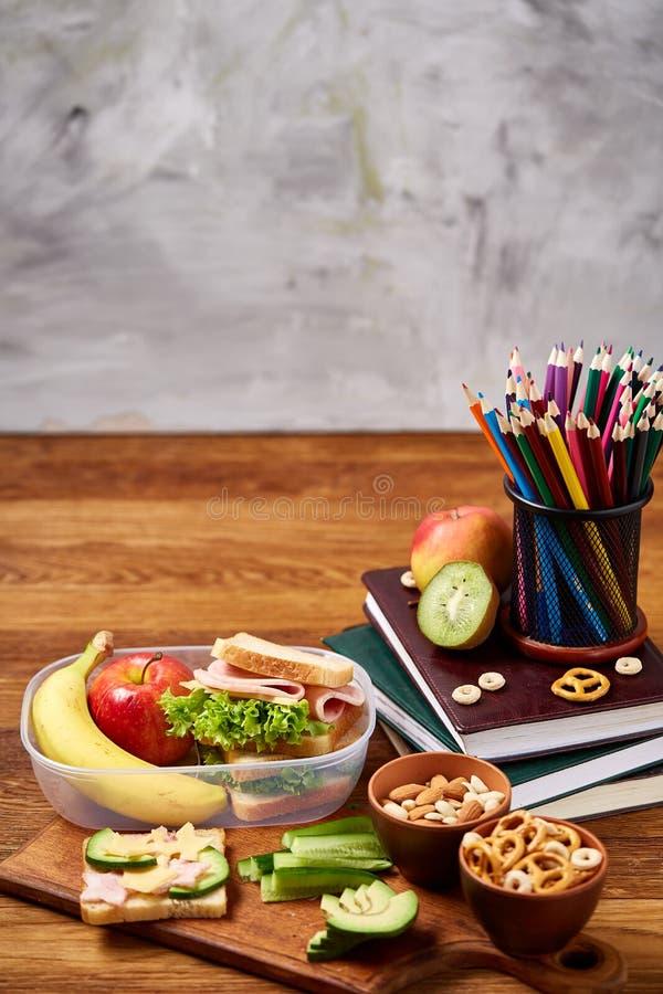 L'école ou la gamelle de pique-nique avec le sandwich et les divers légumes et fruits colorés sur le fond en bois, se ferment  photos libres de droits