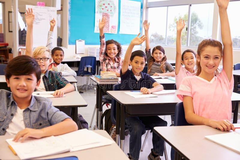 L'école primaire badine dans une salle de classe soulevant leurs mains image libre de droits
