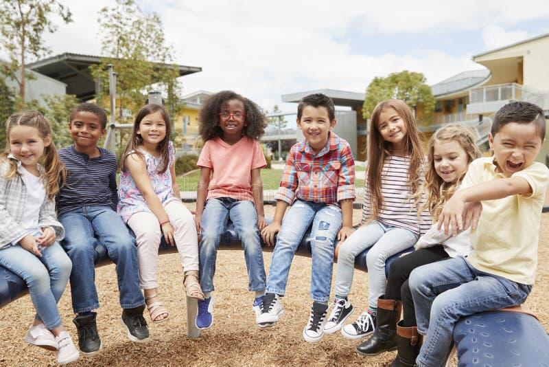 L'école primaire badine se reposer sur le carrousel dans la cour de récréation images libres de droits
