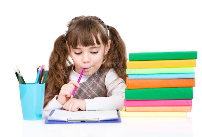 L'écolière écrivent l'essai d'isolement sur le fond blanc photographie stock