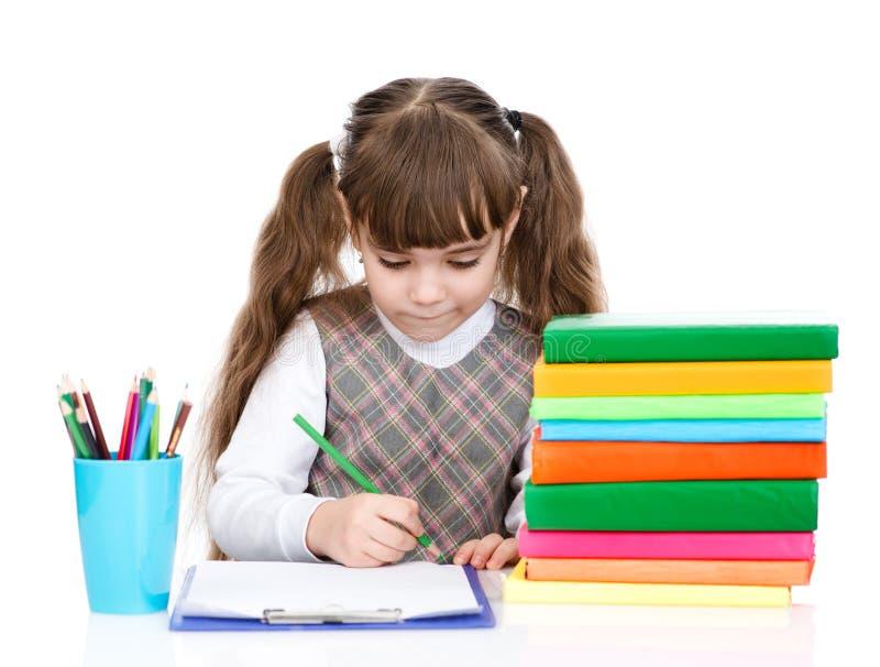 L'écolière écrivent l'essai d'isolement sur le fond blanc images stock