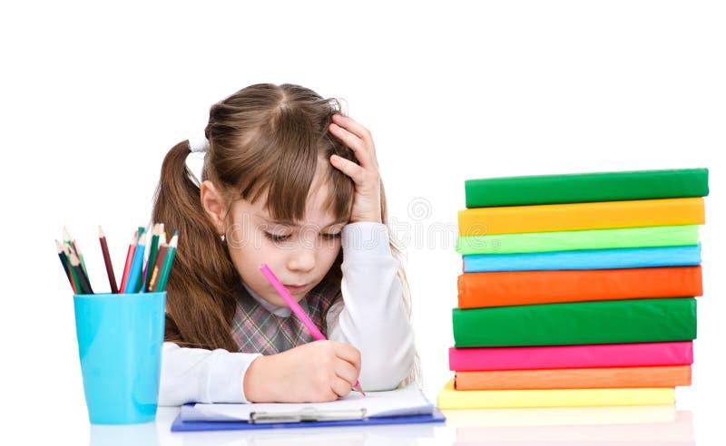 L'écolière écrivent l'essai sur le fond blanc photos libres de droits