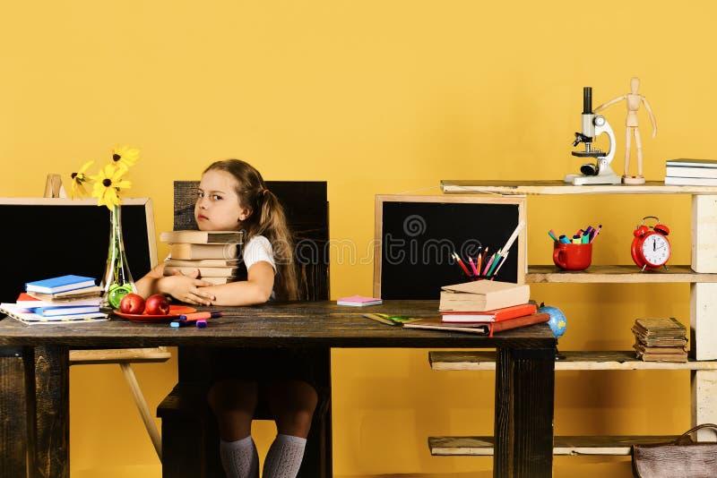 L'écolière avec le visage grincheux tient la pile de livres photographie stock libre de droits