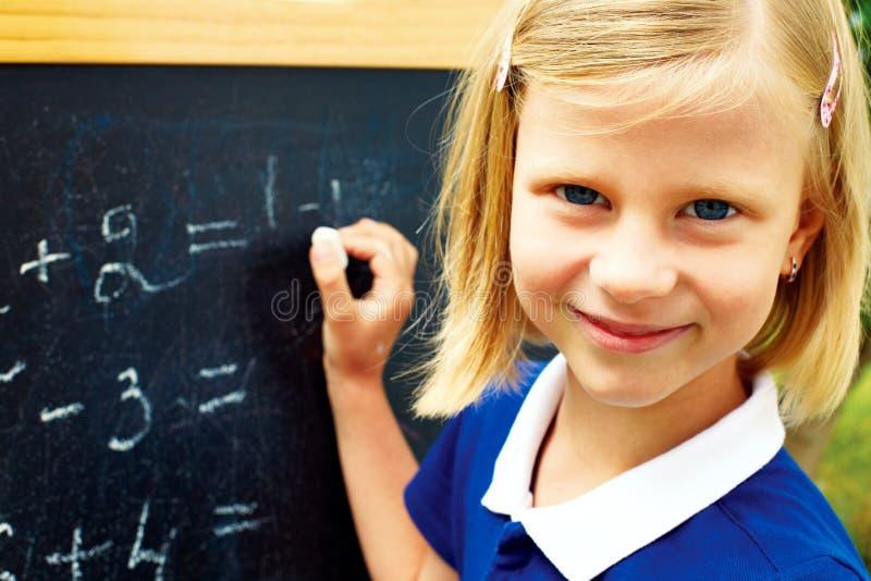 L'écolière considère résoudre un problème mathématique images stock