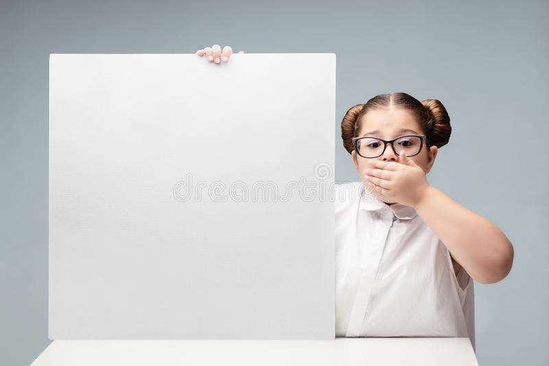 L'écolière de fille montre sur un conseil vide pour la publicité De l'adolescence avec des glaces photo stock