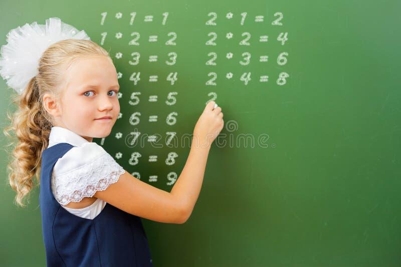 L'écolière de la première catégorie a écrit la table de multiplication sur le tableau noir avec la craie photo stock