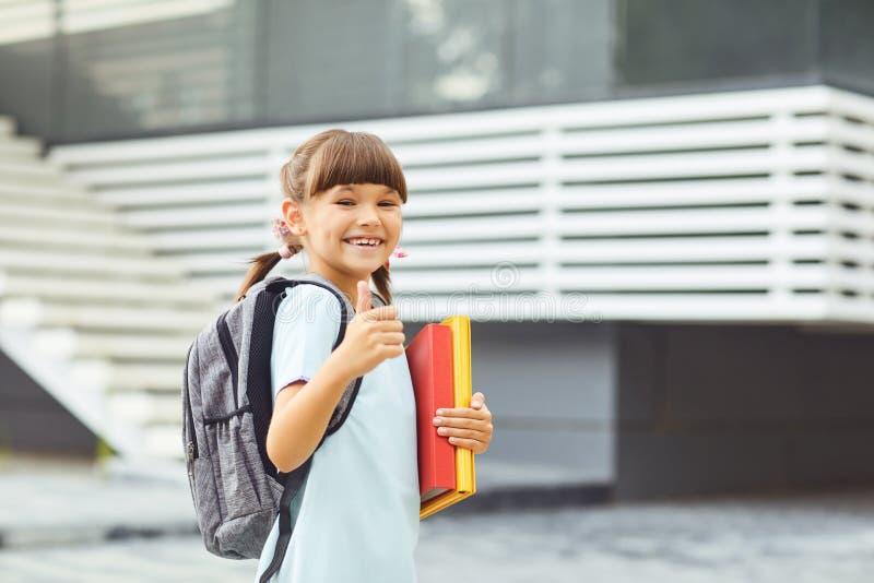 L'écolière de sourire de fille avec un sac à dos va à disposition instruire photos libres de droits