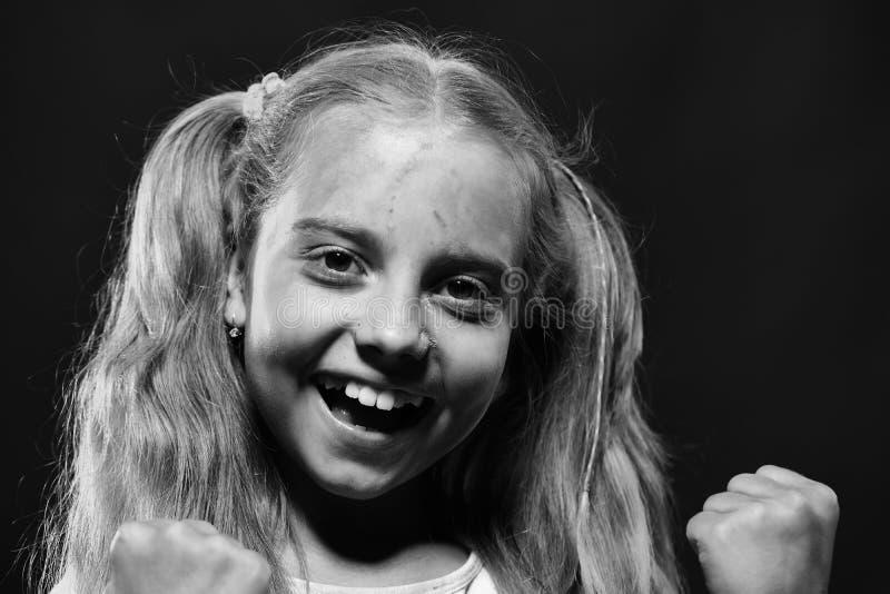 L'écolière a des taches de peinture sur le visage tient des poings  La fille avec le visage heureux se lève sur le fond noir, fin photo stock