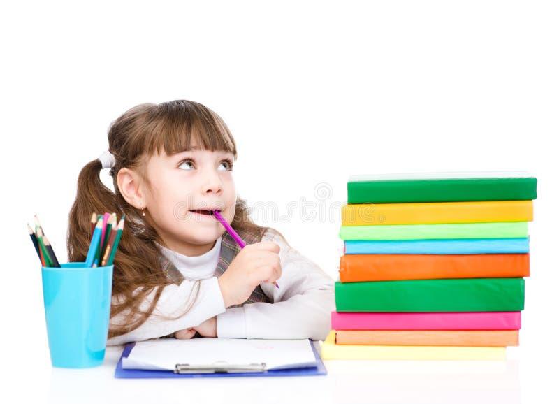 L'écolière réfléchie regardant au côté et se lèvent D'isolement sur le blanc image libre de droits