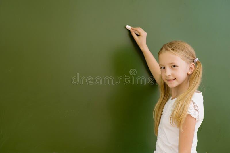 L'écolière veut écrire quelque chose sur le tableau noir photos stock