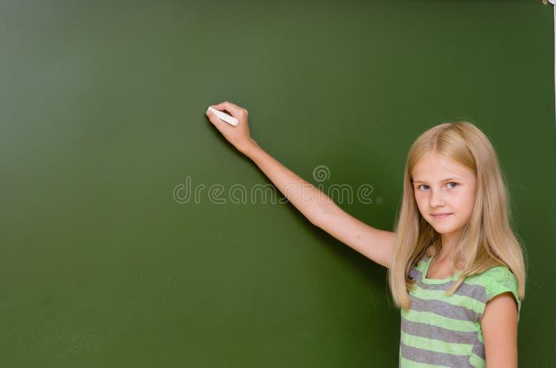 L'écolière veut écrire quelque chose sur le tableau noir photographie stock libre de droits