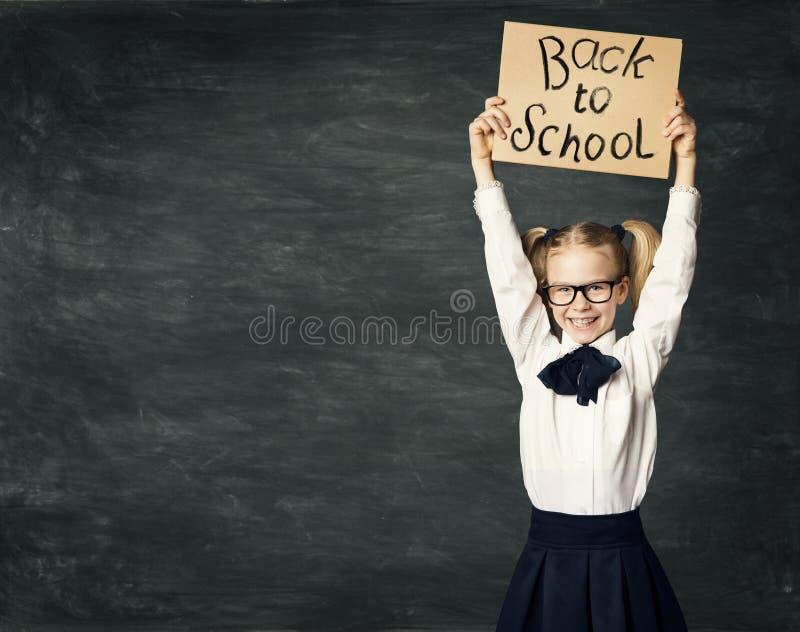 L'écolier au-dessus du fond de tableau noir, fille font de la publicité le conseil photo stock
