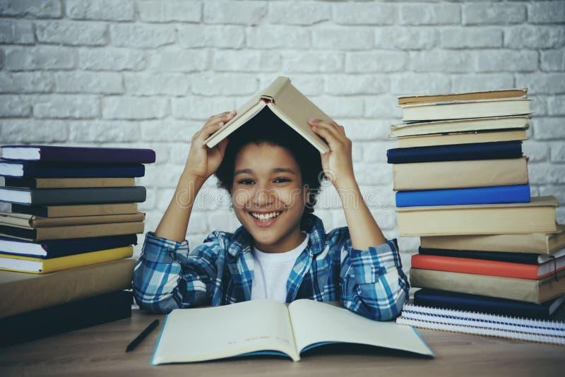L'écolier d'afro-américain tient le livre au-dessus photos stock