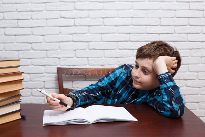L'écolier ennuyé considère au-dessus de la solution de tâche Schoo élémentaire photographie stock libre de droits