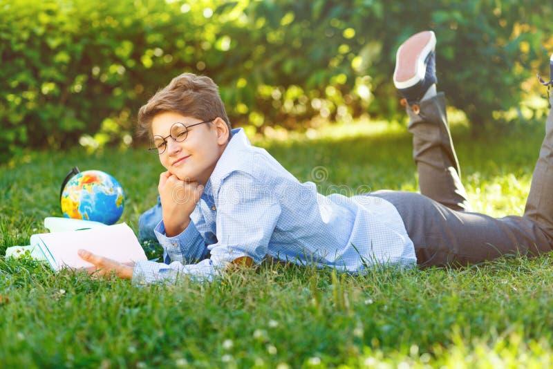 L'écolier mignon et jeune en verres ronds et la chemise bleue se trouve sur l'herbe et tient un livre dans des ses mains, lit en  photo stock