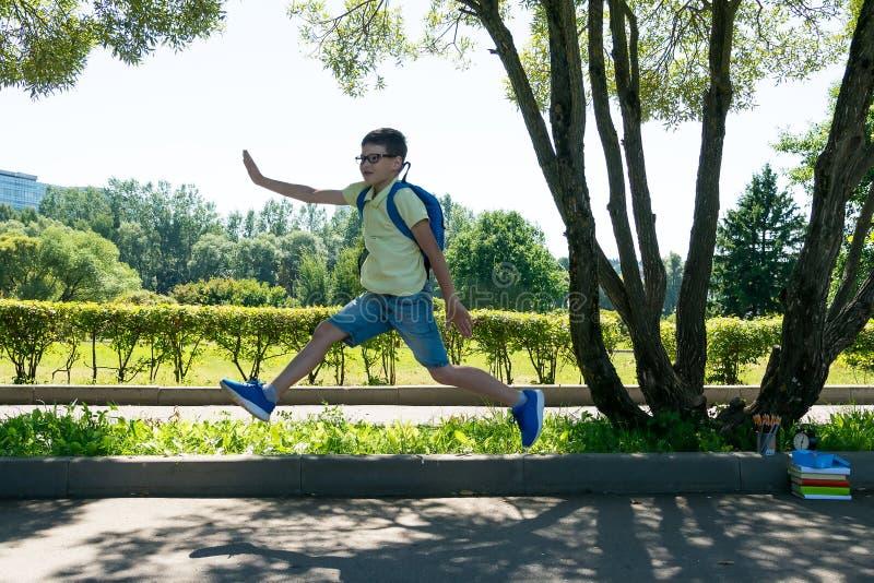 L'écolier a sauté pour la joie en parc que les leçons finies image stock