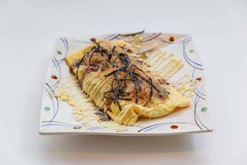 L'écrimage d'Omlette de Japonais avec de la sauce, Mayonaise, Katsuobushi a séché, thon et algue de bonites fermenté et et fumé images libres de droits