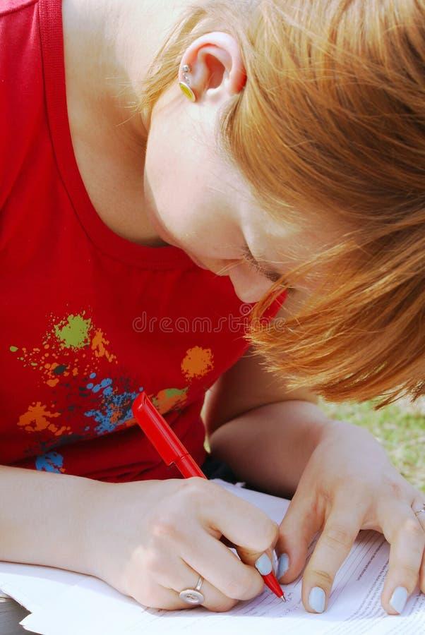 L'écriture d'une fille sur ses genoux photo stock