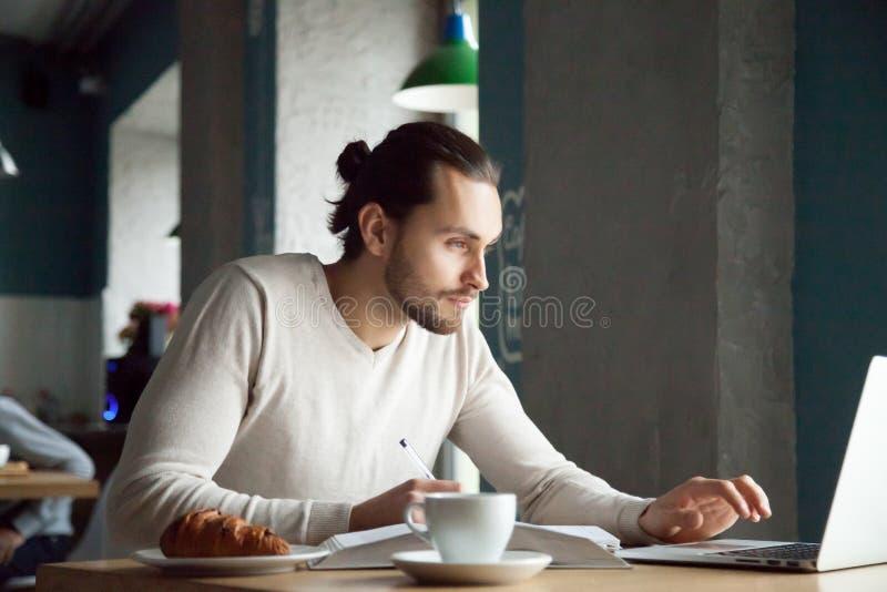 L'écriture focalisée d'homme note l'étude en ligne avec l'ordinateur portable en café image stock