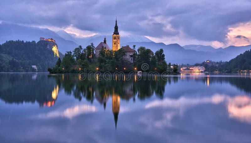 L'église de l'hypothèse dans le lac a saigné avec le château à l'arrière-plan photographie stock libre de droits