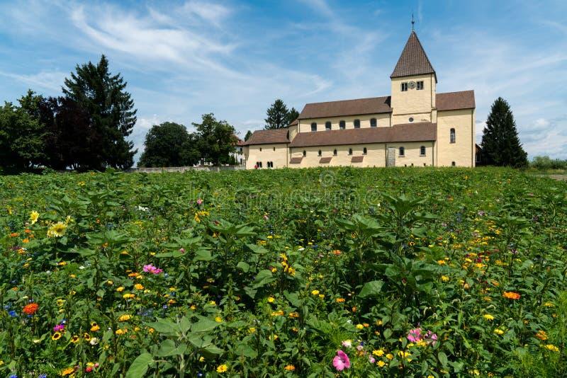 L'église de St Georg sur l'île de Reichenau sur le Lac de Constance avec les wildflowers colorés dans le premier plan photographie stock libre de droits