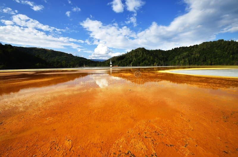 L'église inondée en rouge toxique a pollué le lac dû à l'exploitation de cuivre, village de Geamana, photo stock