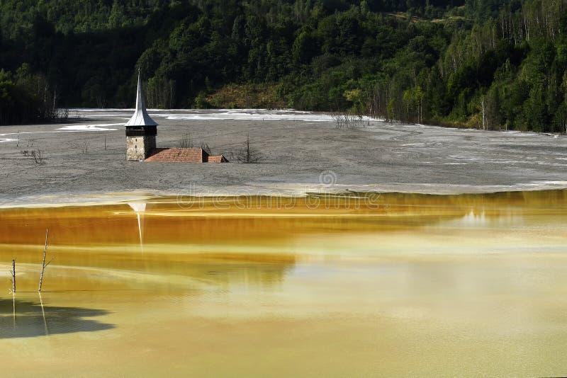 L'église inondée en rouge toxique a pollué le lac dû à l'exploitation de cuivre, village de Geamana, Roumanie desatru naturel photo libre de droits