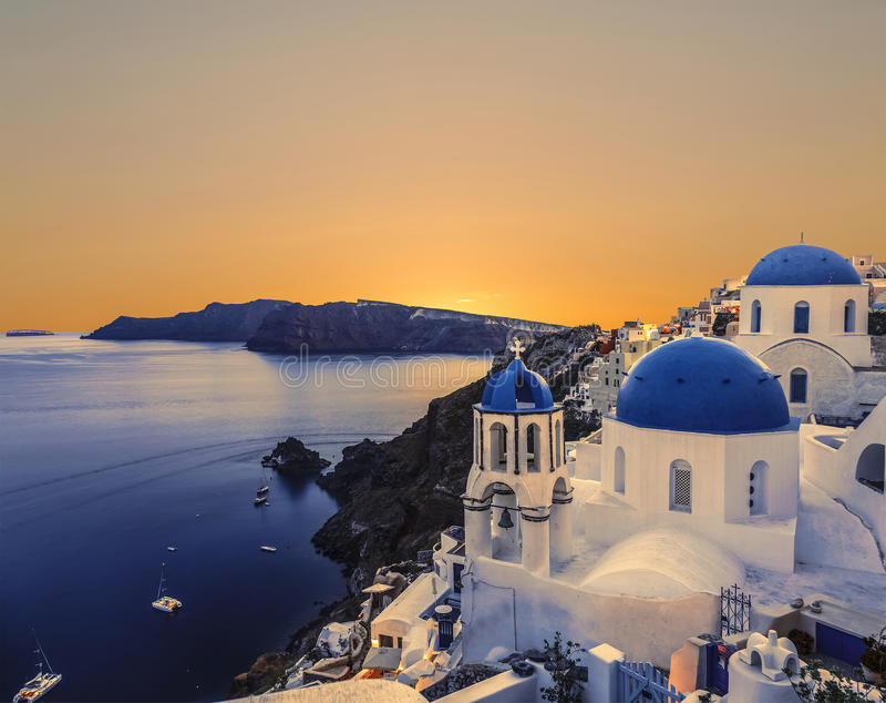 L'église orthodoxe grecque sur les eaux de fond de la mer Égée à Oia au coucher du soleil L'île de Santorin photographie stock