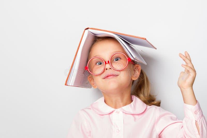 L'élève du cours préparatoire de fille d'Ittle portant des lunettes garde un livre ouvert sur sa tête images libres de droits