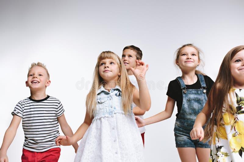 L'élève du cours préparatoire mignon de mode de groupe badine des amis posant ensemble et regardant le fond blanc de caméra photos stock