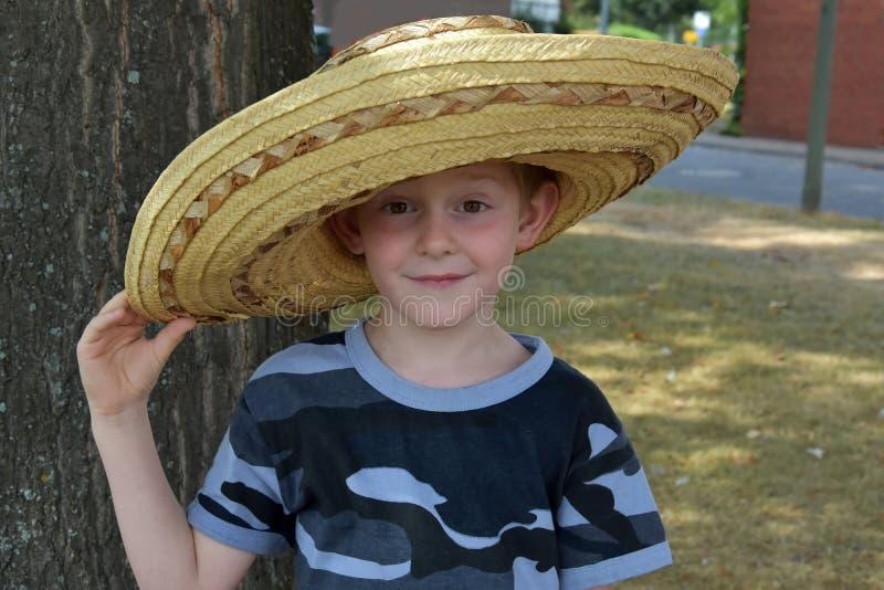 L'élève du cours préparatoire utilise un grand chapeau de paille mexicain photos stock
