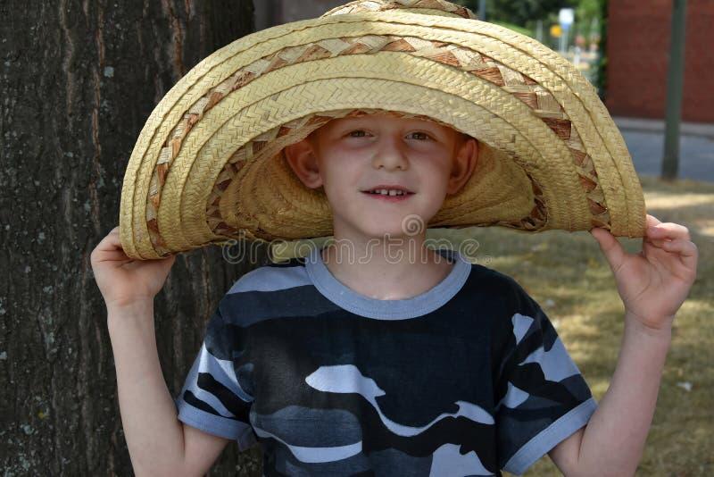 L'élève du cours préparatoire utilise un grand chapeau de paille mexicain image libre de droits