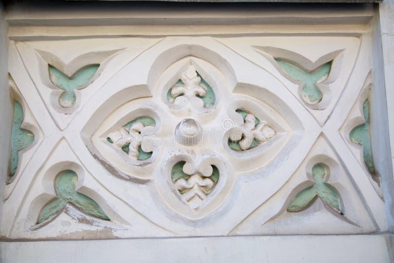 L'élément de finir d'un plâtre de façade Le rectangle à l'intérieur de quatre fleurs aux bords des pétales sont blanc quelques él photographie stock