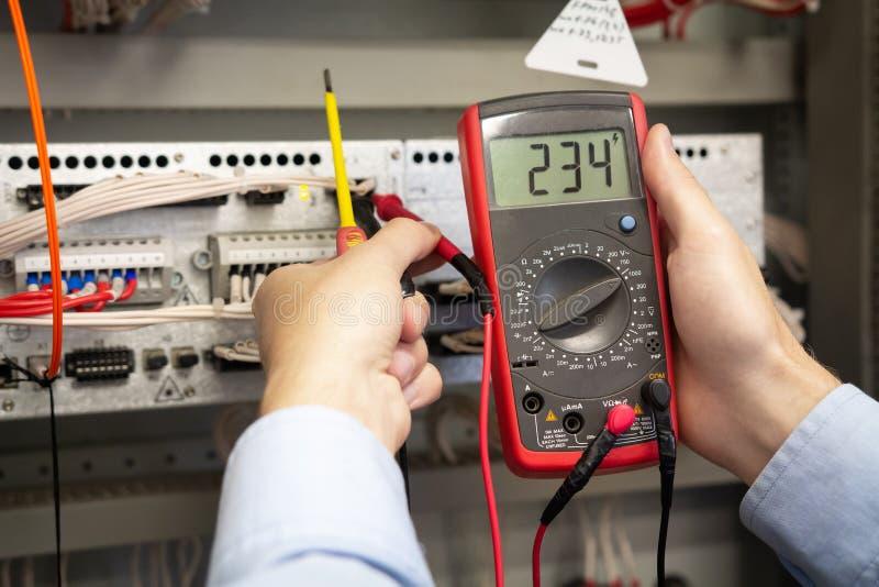 L'électricien ajuste le panneau de commande électrique photos libres de droits