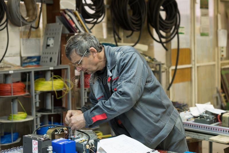 L'électricien assemble et ajuste le panneau de commande électrique Travaux sur assembler le circuit électrique d'a photo libre de droits