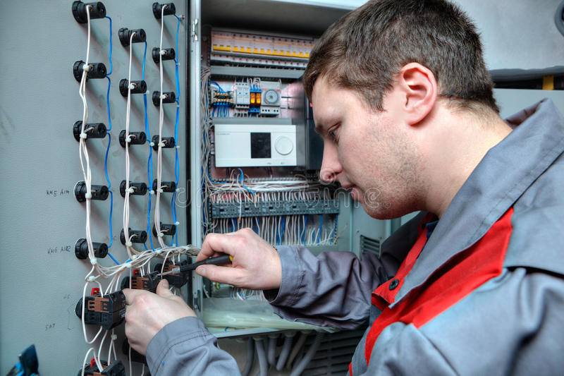 L'électricien d'ingénieur fixe des problèmes dans le panneau électrique images libres de droits