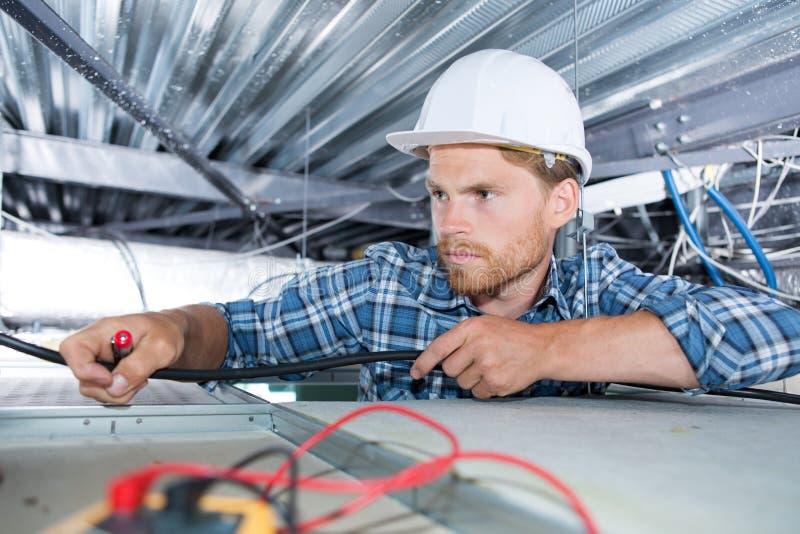 L'électricien place la lampe sur le plafond photos stock