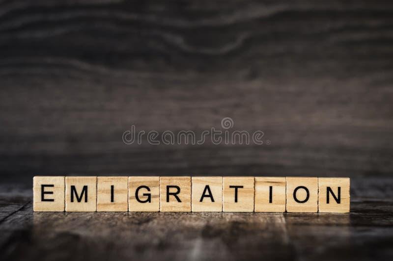 L'émigration de mot est faite de cubes en bois lumineux avec le lett noir images stock