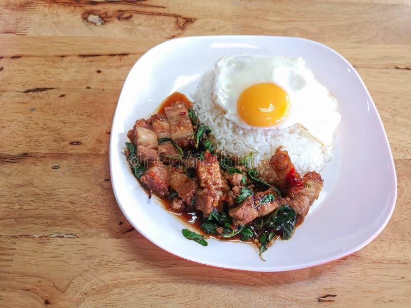 L'émoi a fait frire le porc croustillant épicé avec le basilic et l'oeuf au plat thaïlandais photos libres de droits