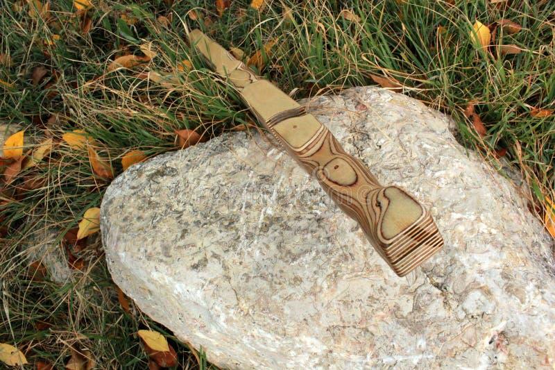 L'épée en bois de gaine se tient sur un support sur une pierre image libre de droits