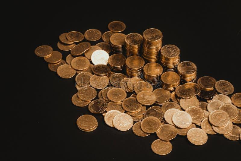 L'épargne, colonnes croissantes des pièces de monnaie, piles des pièces de monnaie disposées comme graphique dans la chambre noir image libre de droits