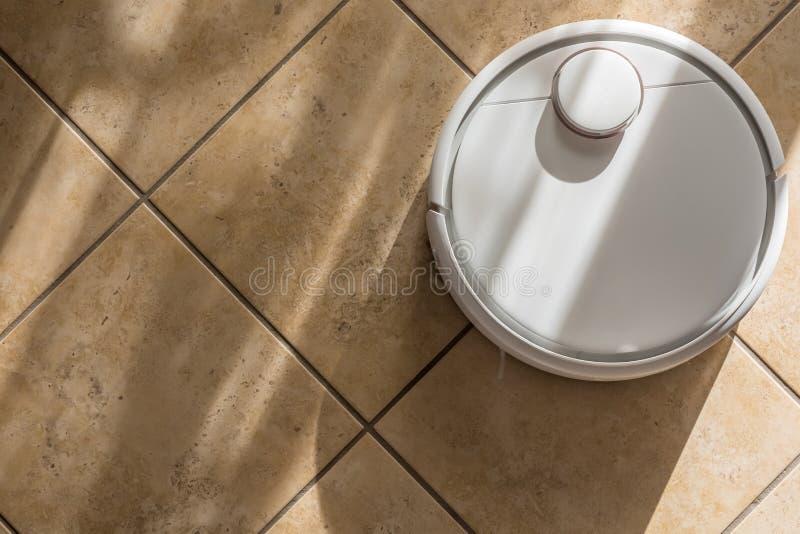L'épargne de temps dans le ménage par le soin de plancher avec un robot intelligent de vide photo stock