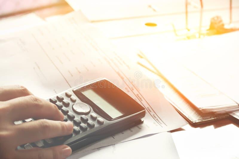 L'épargne, des finances, économie et concept à la maison - fermez-vous de l'homme avec la calculatrice comptant en faisant des no photo stock