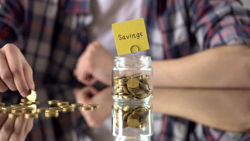 L'épargne exprime au-dessus du pot en verre avec l'argent, les fonds de jour pluvieux, investissement à l'avenir image libre de droits
