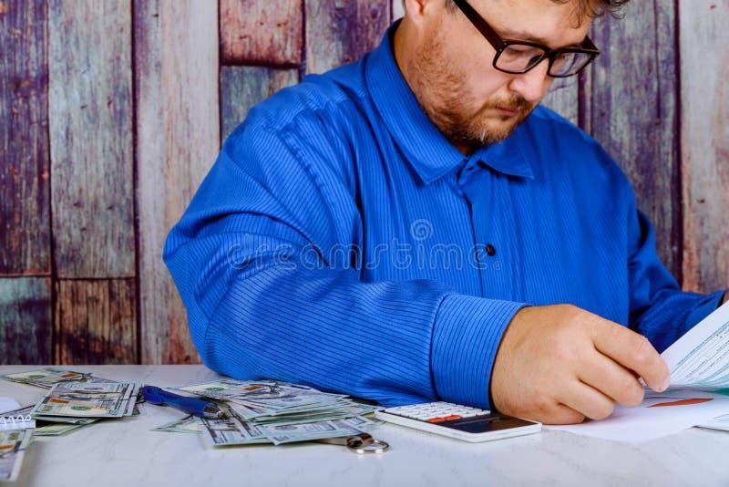 l'épargne, finances, économie et fin à la maison de concept de l'homme avec la calculatrice comptant l'argent et faisant des note photos libres de droits