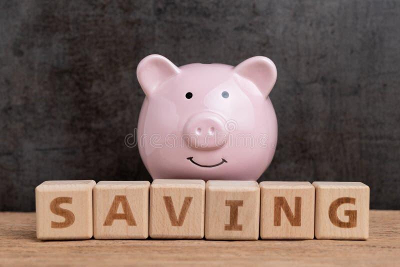 L'épargne heureuse, budget, investissement ou buts financiers concept, tirelire de rose de sourire et pile de mot en bois de bâti photo libre de droits