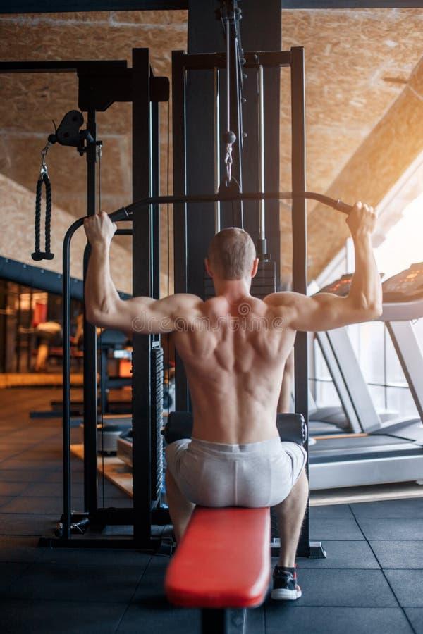 L'épaule abaissent la machine homme établissant la formation d'avancement du film de lat au gymnase Exercice de force de corps su images stock