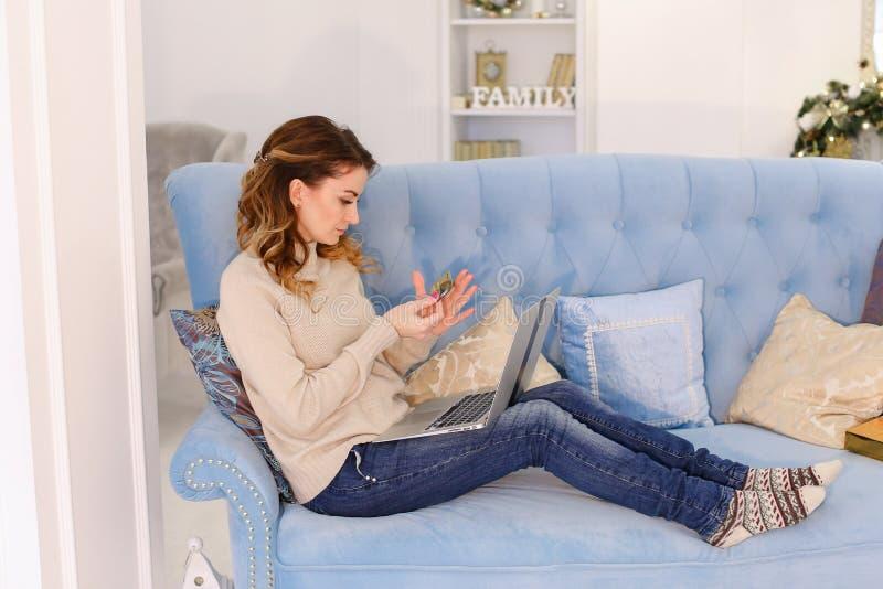 L'épouse de soin choisit le cadeau en ligne sur l'ordinateur portable pour la famille et paye par image stock