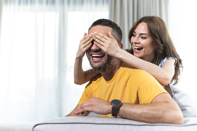 L'épouse riante ferme des yeux de son mari photo stock